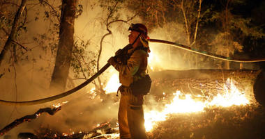FILE - In this Oct. 14, 2017 file photo, a firefighter holds a water hose while fighting a wildfire in Santa Rosa, Calif. Investigators say the deadly 2017 wildfire that killed 22 people in California's wine country was caused by a private electrical syst