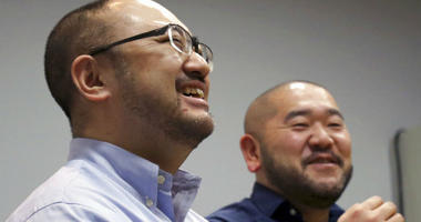 In this Jan. 28, 2019, photo, Kenji Aiba, left, and his partner Ken Kozumi laugh during an interview with The Associated Press in Tokyo.