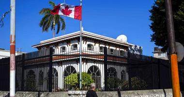 FILE - In this April 17, 2018 file photo, a man walks beside Canada's embassy in Havana, Cuba.