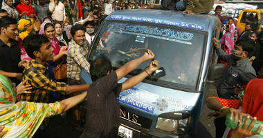 FILE - In this Wednesday, Jan. 9, 2019 file photo, Bangladeshi garment workers vandalize a vehicle during a protest in Savar, on the outskirts of Dhaka, Bangladesh.
