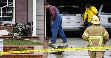 A resident looks at debris that hit a house after a small plane crashed into a neighborhood of Yorba Linda, Calif.