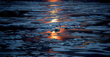 FILE- In this July 23, 2017, file photo the midnight sun shines across sea ice along the Northwest Passage in the Canadian Arctic Archipelago.