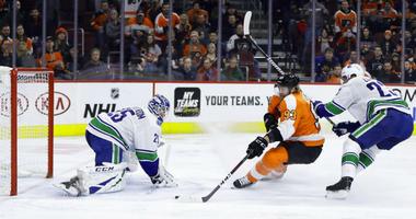 Philadelphia Flyers' Jakub Voracek (93) scores a goal against Vancouver Canucks' Jacob Markstrom (25) as Alexander Edler (23) defends during the second period of an NHL hockey game, Monday, Feb. 4, 2019, in Philadelphia.
