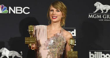 """FILE - In this May 20, 2018 file photo, Taylor Swift poses in the press room with the award for top female artist and the award for top selling album for """"reputation"""" at the Billboard Music Awards at the MGM Grand Garden Arena in Las Vegas."""