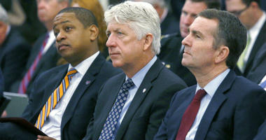 FILE - In this Dec. 18, 2017 file photo, from left, Lt. Governor-elect Justin Fairfax, Attorney General-elect Mark Herring and Governor-elect Ralph Northam listen as Virginia Governor Terry McAuliffe addresses a joint meeting of the House and Senate money