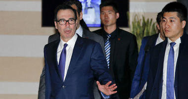 U.S. Treasury Secretary Steven Mnuchin, left, gestures to journalists as he leaves a hotel to attend a new round of high-level trade talks with Chinese officials in Beijing, Thursday, Feb. 14, 2019.