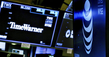 The logos for Time Warner and AT&T appear above alternate trading posts on the floor of the New York Stock Exchange.