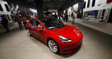 FILE - In this Feb. 9, 2019, file photograph, buyers look over a Model 3 in a Tesla store in Cherry Creek Mall in Denver.