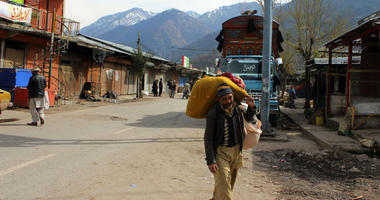 A Pakistani Kashmiri carries his belonging and walks through a market at his hometown in Chakoti on the violent border that separates the Himalayan region of Kashmir between Pakistan and India, Saturday, March 2, 2019.