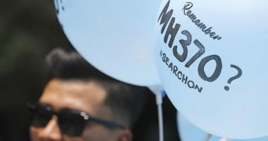 A volunteer gives out balloons printed with MH370 during a Day of Remembrance for MH370 event in Kuala Lumpur, Malaysia, Sunday, March 3, 2019.