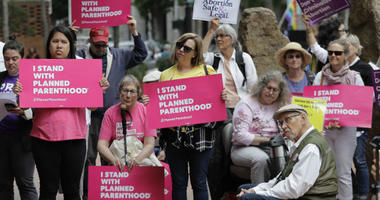 FILE - In this July 10, 2018 file photo, protesters hold signs supporting Planned Parenthood in Seattle, as they demonstrate against President Donald Trump and his choice of federal appeals Judge Brett Kavanaugh as his second nominee to the Supreme Court.