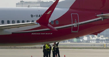Ground crew chat near a Boeing 737 MAX 8 plane operated by Shanghai Airlines parked on tarmac at Hongqiao airport in Shanghai, China, Tuesday, March 12, 2019.