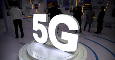 Visitors stand near a 5G logo at a display the PT Expo in Beijing.