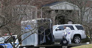 Crime scene investigators load a car that appears to have been checked for fingerprints onto a flatbed truck in the Staten Island borough of New York, Thursday, March 14, 2019.