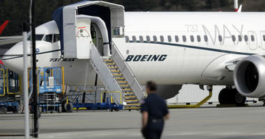 A worker walks next to a Boeing 737 MAX 8 airplane parked at Boeing Field, Thursday, March 14, 2019, in Seattle.