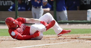 Philadelphia Phillies' Bryce Harper rolls on the dirt holding his leg after getting hit by a pitch against the Toronto Blue Jays during the sixth inning in a spring training baseball game, Friday, March 15, 2019, in Clearwater, Fla.