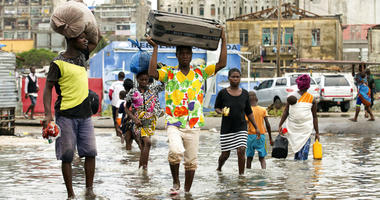 People carry their personal effects after Tropical Cyclone Idai, in Beira, Mozambique.