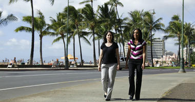 Diane Cervelli, left, and Taeko Bufford, right, walk past Waikiki beach in Honolulu.