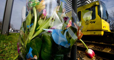 A tram passes flowers placed at the site of a shooting incident on a tram, in Utrecht, Netherlands.
