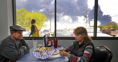 Charlie Tamez and his wife, Dalia Tamez, finish their lunch at Ken's Restaurant, 1122 Center St., as the chemical fire at Intercontinental Terminals Company continues to send dark smoke over Deer Park, Texas.