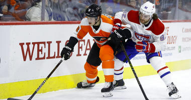 Philadelphia Flyers' Travis Sanheim, left, and Montreal Canadiens' Jonathan Drouin battle for the puck during the first period of an NHL hockey game.