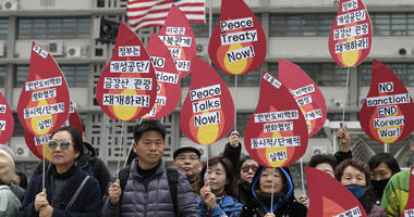 Protesters hold signs during a rally demanding the denuclearization of the Korean Peninsula and peace treaty near the U.S. embassy in Seoul, South Korea, Thursday, March 21, 2019.