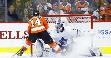 Philadelphia Flyers' Sean Couturier, left, scores past Toronto Maple Leafs' Frederik Andersen during the shootout in an NHL hockey game Wednesday, March 27, 2019, in Philadelphia. Philadelphia won 5-4.