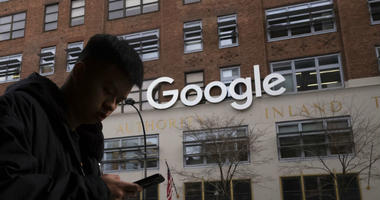 A man using a mobile phone walks past Google offices in New York. Executives from Google and Facebook are facing Congress Tuesday, April 8, 2019, to answer questions about their role in the hate crimes and the ris