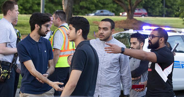People gather across from the campus of University of North Carolina at Charlotte after a shooting at the school Tuesday, April 30, 2019, in Charlotte, N.C.