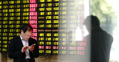 A man looks at his smartphone near a display showing stock prices at a brokerage house in Shanghai Monday, May 6, 2019.