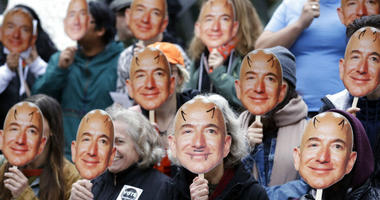"FILE - In this Oct. 31, 2018, file photo, demonstrators hold images of Amazon CEO Jeff Bezos near their faces during a Halloween-themed protest at Amazon headquarters over the company's facial recognition system, ""Rekognition,"" in Seattle."