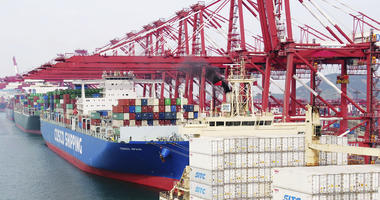 A barge pushes a container ship to the dockyard in Qingdao.