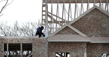 Construction workers build new housing.