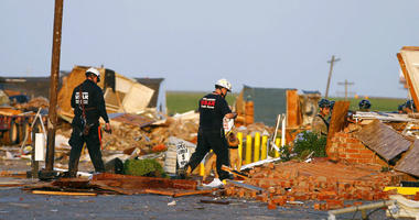 Workers look through tornado damage at the American Budget Value Inn in El Reno, Okla., Sunday, May 26, 2019. The deadly tornado leveled a motel and tore through the mobile home park near Oklahoma City overnight