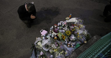 A man pays respects at a makeshift memorial.