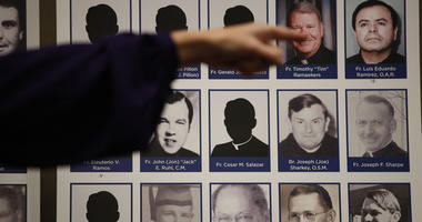 Victim points to photos of Catholic priests accused of sexual misconduct.