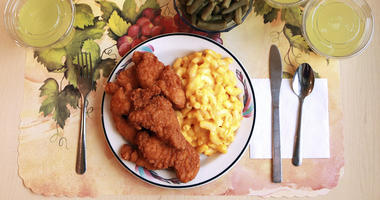 """This undated photo provided by the National Institutes of Health in June 2019 shows an """"ultra-processed"""" lunch including brand name macaroni and cheese, chicken tenders, canned green beans and diet lemonade."""