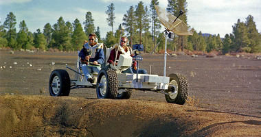 This undated photo provided by the U.S. Geological Survey Astrogeology Science Center shows Apollo 15 astronauts Jim Irwin, left, and Dave Scott driving a prototype of a lunar rover in a volcanic cinder field east of Flagstaff, Ariz.