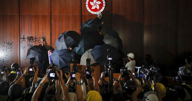 Protesters in Hong Kong took over the legislature's main building Monday night, tearing down portraits of legislative leaders and spray painting pro-democracy slogans on the walls of the main chamber.