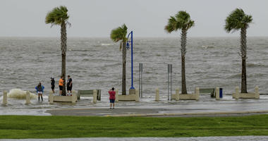 People check out the waves on Lakeshore Drive in New Orleans, La., Friday, July 12, 2019, as water moves in from Lake Pontchartrain from the storm surge from Tropical Storm Barry in the Gulf of Mexico.