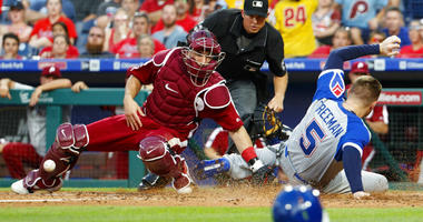 Atlanta Braves' Freddie Freeman, right, slides home safely as Philadelphia Phillies catcher J.T. Realmuto, left, is unable to keep control of the ball during the third inning of a baseball game, Saturday, July 27, 2019, in Philadelphia.