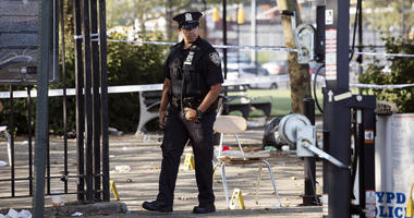A police officer walks by yellow evidence markers at a playground in the Brownsville neighborhood in the Brooklyn borough of New York, Sunday, July 28, 2019.