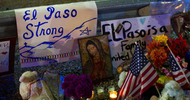 A Virgin Mary painting, flags and flowers adorn a makeshift memorial for the victims of Saturday's mass shooting at a shopping complex in El Paso, Texas, Sunday, Aug. 4, 2019.
