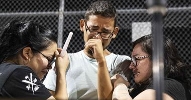 Three Walmart workers, Melisa Gonzalez, Jesus Romero and Raven Ramos, who helped people to escape during the mass shooting on Saturday, Aug. 3, 2019, get emotional during during a vigil at Ponder Park in honor of the shooting victims in El Paso, Texas.