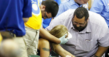 FILE - In this July 6, 2015, file photo, a fan is helped after being hit by a foul ball during the ninth inning of a baseball game between the Milwaukee Brewers and the Atlanta Braves in Milwaukee.