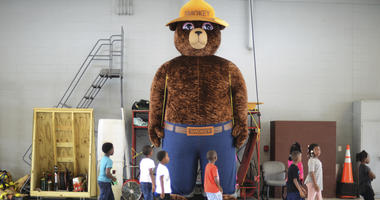 In this Wednesday, Oct. 11, 2017 file photo, a giant Smokey Bear statue greets children at the Fire Department Open House at Fire Station One in Kinston, N.C.