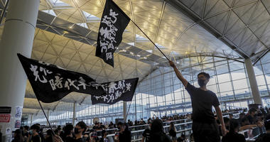 Protesters wave flags at the Hong Kong International Airport, Monday, Aug. 12, 2019. One of the world's busiest airports canceled all flights after thousands of Hong Kong pro-democracy protesters crowded into the main terminal Monday afternoon.