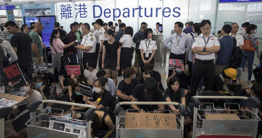 Airport security personnel stand guard as travelers walk past protesters holding a sit-in rally at the departure gate of the Hong Kong International Airport in Hong Kong, Tuesday, Aug. 13, 2019.