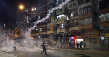 Protesters react to tear gas from Shum Shui Po police station in Hong Kong on Wednesday, Aug. 14, 2019.