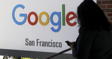 In this May 1, 2019, file photo, a person walks past a Google sign in San Francisco.